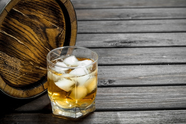 Whiskey in a glass with ice cubes and a barrel. on wooden