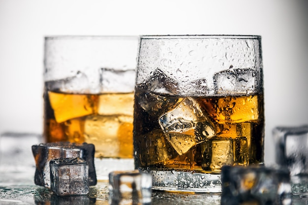 Whiskey in a glass with ice on a light background