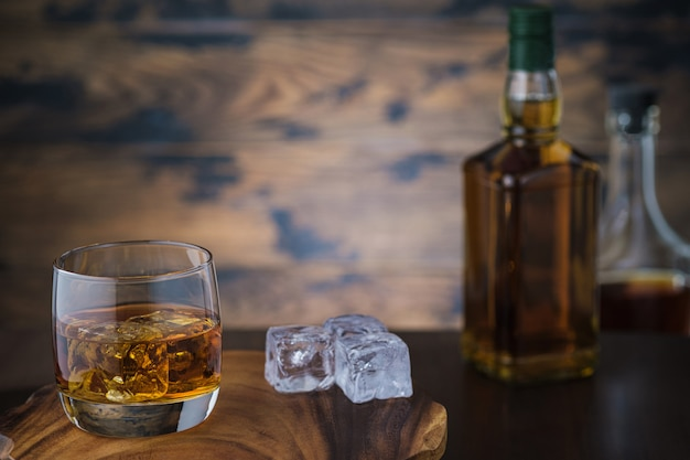 Whiskey and ice cubes and two bottles with brandy or scotch