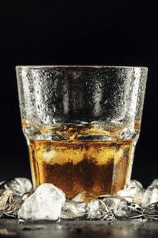 Whiskey and ice on dark background