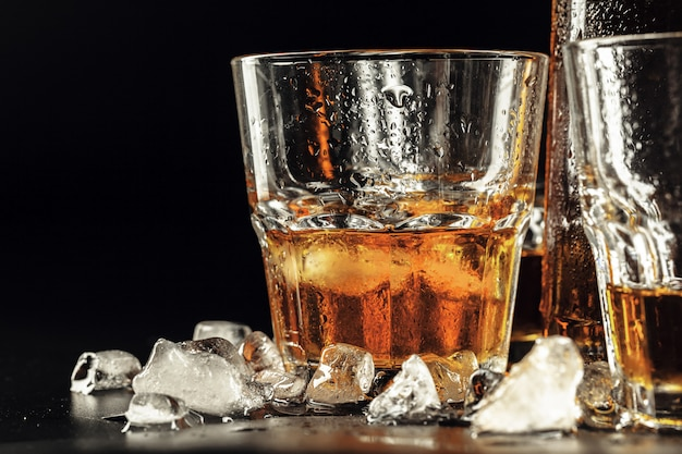 Whiskey and ice on rustic wood