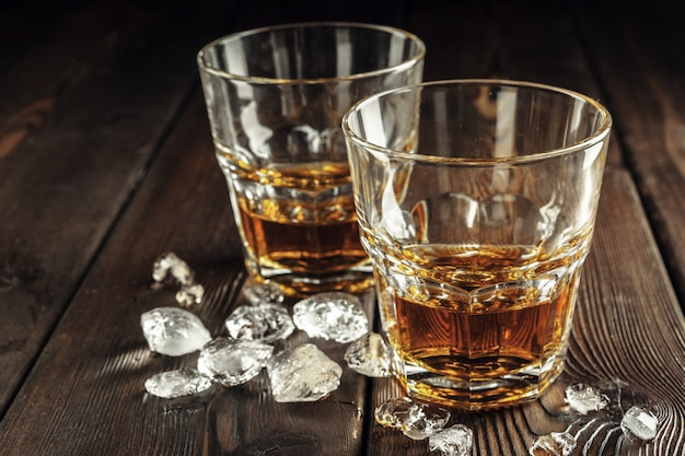 Whiskey and ice on rustic wooden table