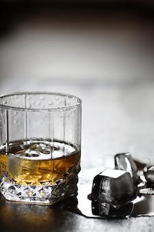 유리잔에 든 위스키와 나무 탁자에 있는 얼음 조각