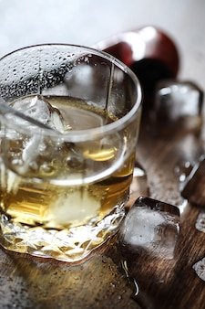ガラスのウイスキーと木製のテーブルの上の氷のかけら