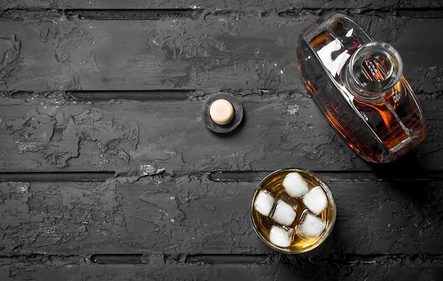 ガラス瓶と氷のガラスのウイスキー。黒の素朴な