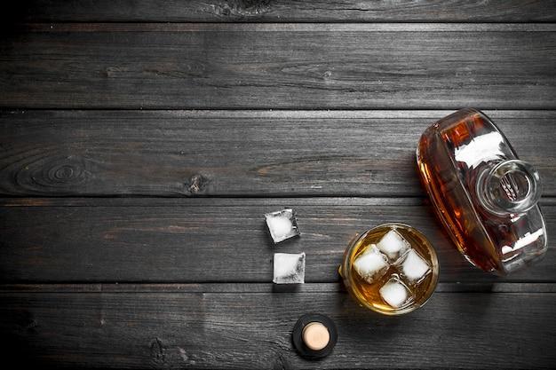 ガラス瓶とグラスに入ったウイスキー。木製に