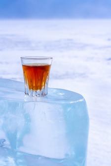 Виски в стакане стоит на ледяном блоке оранжевый алкогольный напиток в стакане