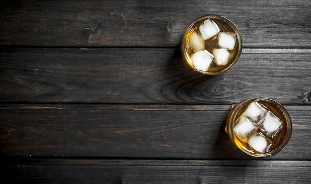角氷とグラスのウイスキー。黒い木製に