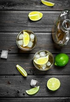グラスに入ったウイスキーとライムスライスのボトル。黒い木製のテーブルの上