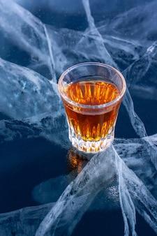小さなガラスのウイスキーは、氷にひびが入ったバイカル湖の透明な氷の上に立っています