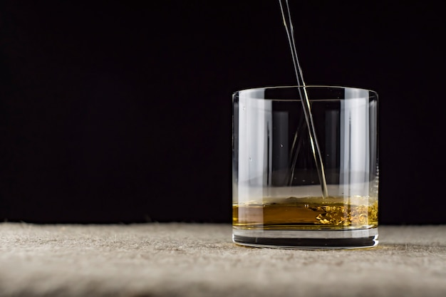 Whiskey is poured into a glass