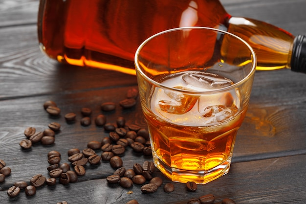 Whiskey or liqueur, coffee beans and orange cut on wooden . seasonal holidays .