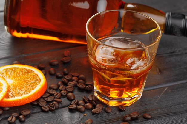 Whiskey or liqueur, coffee beans and orange cut on wooden.