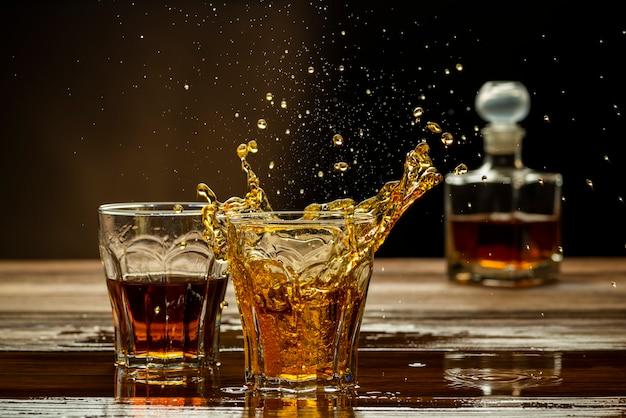 グラスに飛び散るテーブルのウィスキー、強いアルコール飲料