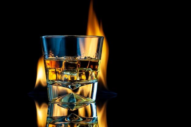 火のある黒の上に角氷が付いた透明なガラスのウイスキーまたはバーボン
