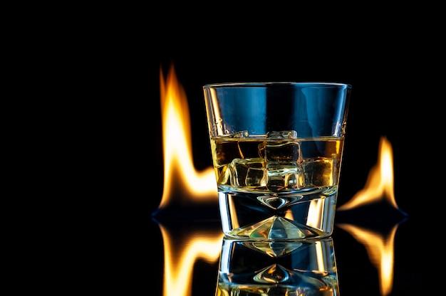 Виски или бурбон в прозрачном стакане с кубиками льда на черном с огнем