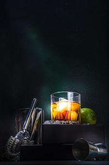 Виски или коньяк в стакане, с лаймом, кубиками льда и посудой для барменов, темный фон с копией пространства на подставке