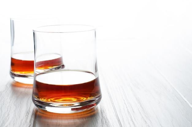 Виски или коньяк или бренди в стеклянном стакане на белом деревянном столе.