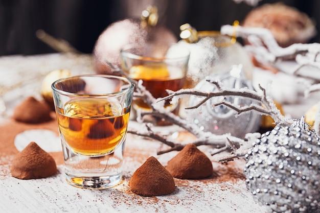 Виски или ликер, трюфельные шоколадные конфеты в какао-порошке и рождественские украшения на белом деревянном фоне.