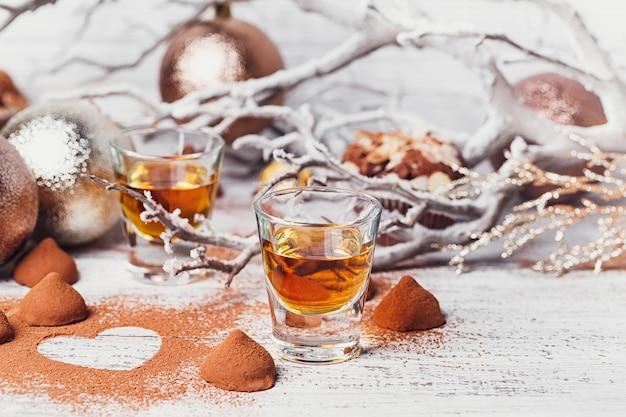 ウイスキーまたはリキュール、ココアパウダーのトリュフチョコレート菓子、白い木製の背景にクリスマスの装飾。