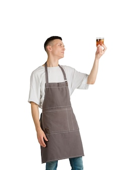 Whiskey portrait of a young male caucasian barista or bartender in brown apron smiling