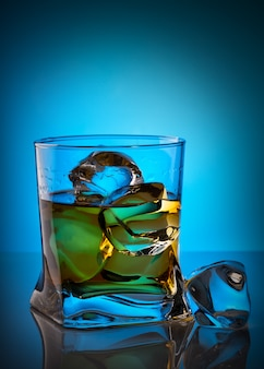 Whiskey in transparent glass with ice cube lying on glass table