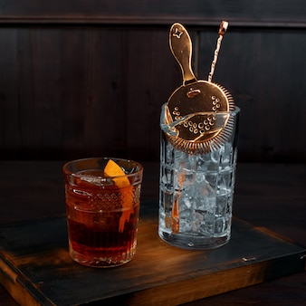 クリスタルガラスにオレンジのスライスが入ったウイスキーは、氷とカクテルを作るためのプロの道具が入ったガラスの隣のバーのテーブルにあります。スパイスの効いた濃い飲み物。