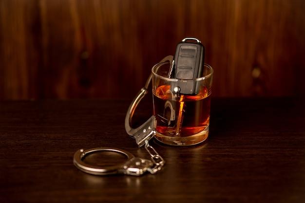 車のキーと手錠が付いているウイスキー。飲酒運転のコンセプト。