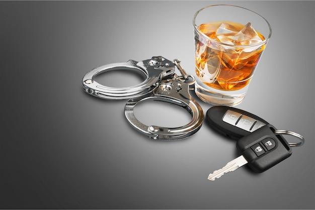 음주와 운전을 위한 자동차 열쇠와 수갑 개념이 있는 위스키