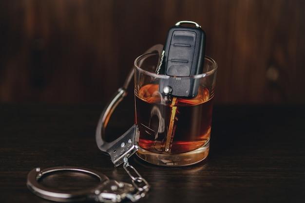 車のキーと手錠が付いているウイスキー。