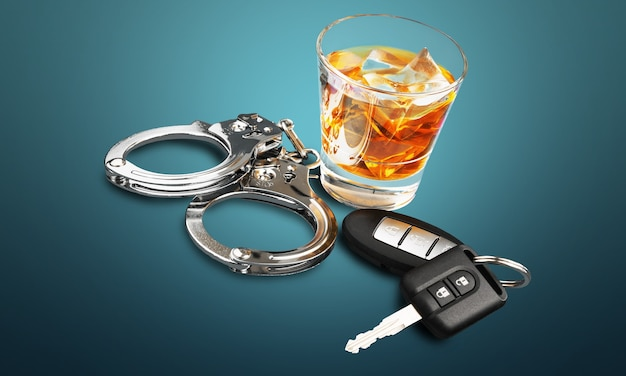 Whiskey with car keys and handcuffs concept for drinking and driving