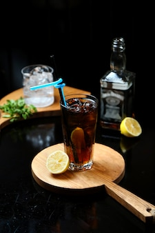Whiskey with cola on wooden board