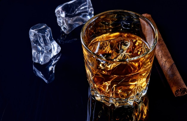 Whiskey with ice or brandy in glass with cigar on black background