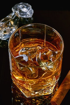 Whiskey with ice or brandy in glass with cigar on black table. whisky with ice in glass. whiskey or brandy. selective focus.