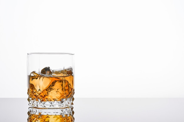 Whiskey with ice or brandy in glass with cigar on white table. whisky with ice in glass. whiskey or brandy. selective focus.