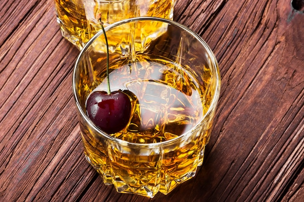 Whiskey with ice and cherry in two glasses