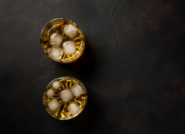 Whiskey with ice on the concrete, top view