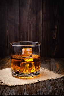 Whiskey with ice cube in a glasses on a rustic dark wooden table