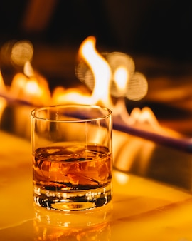 Whiskey with ice cubes over fireplace