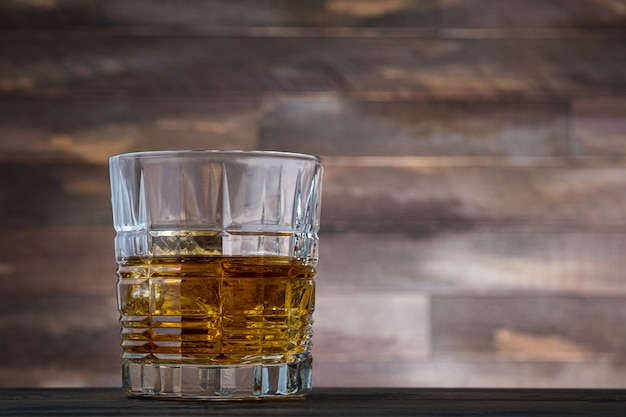 Whiskey with ice cubes in glass on wooden wall