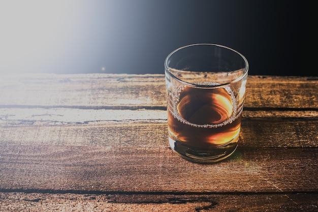 ログテーブルのロックグラスに角氷とウイスキー