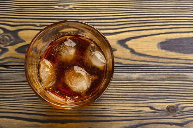 Whiskey with ice cubes on wooden surface