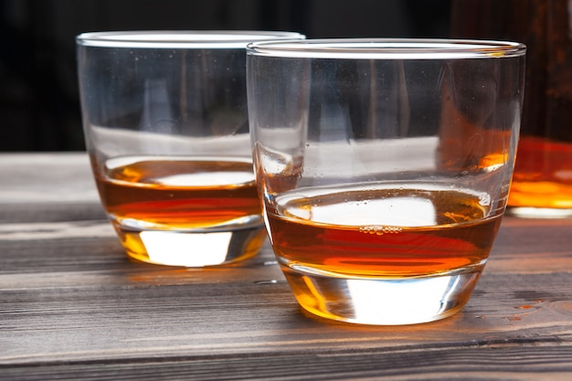Whiskey with ice cubes on wooden table