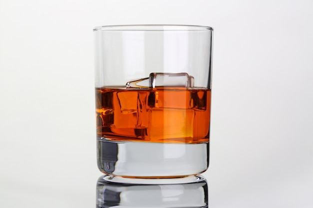 Whiskey with ice in glass beaker on