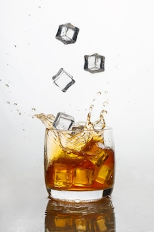 Whiskey with ice in a glass with splashes