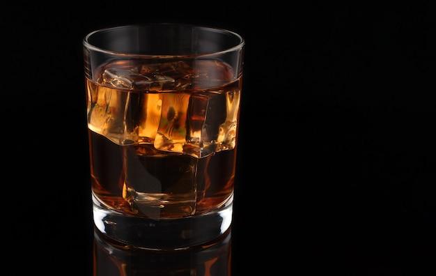 暗いウイスキーと氷の上に氷とウイスキー Premium写真