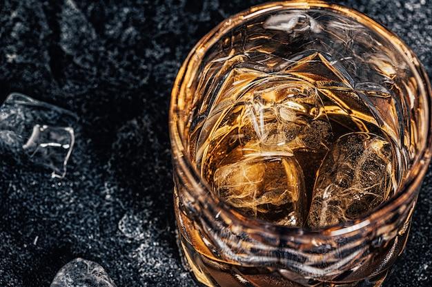 石の暗い背景に氷とウイスキー。