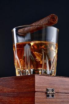 黒い背景に葉巻を入れたグラスに氷やブランデーを入れたウイスキー。グラスに氷を入れたウイスキー。ウイスキーやブランデー。選択と集中。