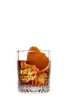 흰색 배경에 격리된 유리에 오렌지가 든 얼음이나 브랜디가 있는 위스키. 유리에 얼음을 넣은 위스키 음료. 위스키나 브랜디. 선택적 초점입니다.