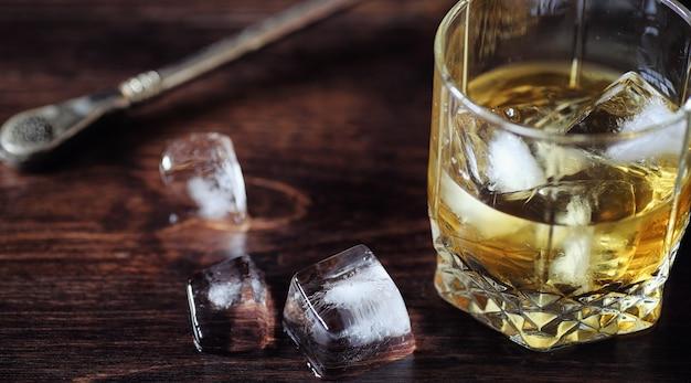 유리에 얼음을 넣은 위스키. 나무 테이블에 얼음 조각과 차갑게 강한 알코올이 든 유리. 미국 위스키, 버번, 카드가 있는 테이블.